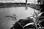 Dourados, Guarani reserve. A child diving, in one of the places that adolescents go to commit suicide by hanging themselves in the trees..