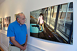 Huntington, New York, USA. August 1, 2015. GEORGE CARRANO looks at a photograph by Aaliyah Colon of a girl running, at the Reception for Project Lives exhibition at fotofoto gallery. Over 200 residents throughout 15 New York Public Housing projects were given single use film cameras to photograph what's important to them in their world. The photography project was originated by Carrano and the book Project Lives was edited by Carrano, C. Davis and J. Fisher, with all royalties from its sale to be donated to resident programs at NYC Housing Authority. The gallery is on the Gold Coast of Long Island.