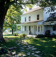 A view from the garden to the porch of this 1770 clapboard farmhouse in Dutchess County, New York.