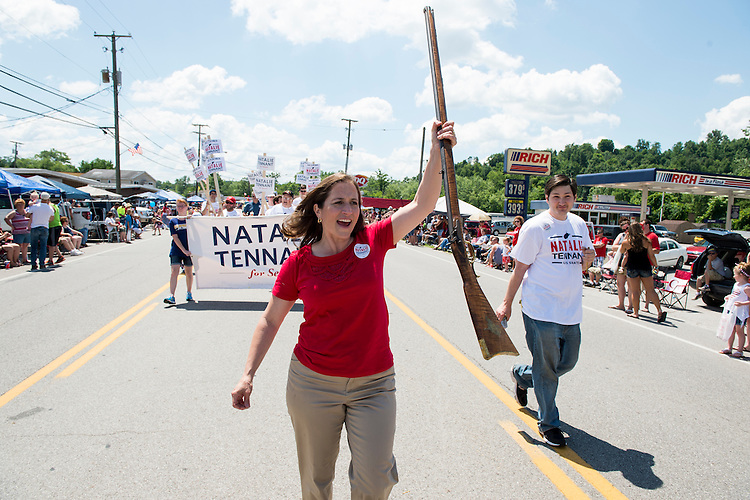 """UNITED STATES - JULY 4: U.S. Senate candidate West Virginia Secretary of State Natalie Tennant marches with her musket in the Ripley 4th of July Parade in Ripley, W. Va., on July 4, 2014. The parade is billed as """"the USA's largest small town Independence Day Celebration. Tennant was selected in 1990 as the first woman to represent the University of West Virginia as the Mountaineers' mascot.(Photo By Bill Clark/CQ Roll Call)"""