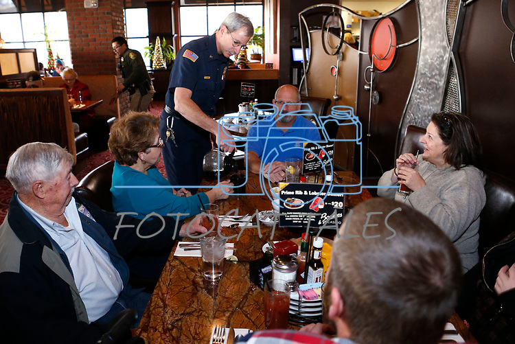 Dave Ruben, with Carson City Fire, serves coffee as first responders from around the area wait on diners at Bodines and SlotWorld as part of the Feast with a Hero fundraiser in Carson City, Nev., on Saturday, Dec. 15, 2018. <br /> Photo by Cathleen Allison/Nevada Momentum