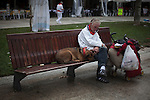 A man and his dog sleeping in a park during San Fermin festival 2014, in Pamplona, Spain. People from around the world arrive to Pamplona every year to take part in the running bulls of San Fermin. Photo by Jose Luis Cuesta.