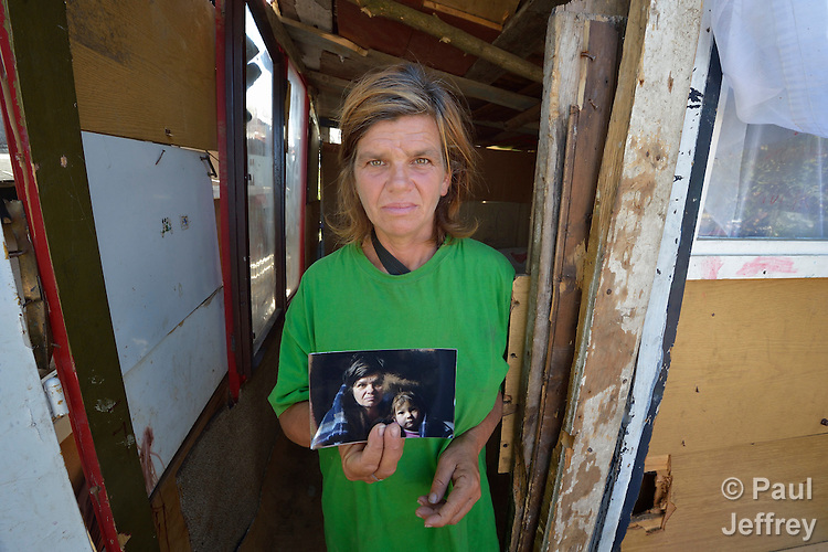 Sofija Arbanac stands in front of her makeshift home in Palilula, a neighborhood of Belgrade, Serbia. She is Roma, and her family was expelled in 2012 from the center of Belgrade to make way for new apartments and office buildings. She is holding a photo of herself and her daughter taken of them a year earlier in the home in Belgrade's center.