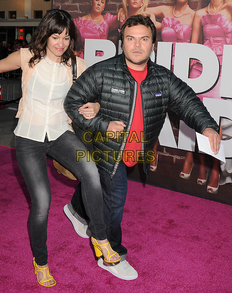 "TANYA HADEN & JACK BLACK.The premiere of ""Bridesmaids"" held at Mann Village Theatre in Westwood, California, USA..April 28th, 2011.full length jeans denim married husband wife arms linked white sheer sleeveless top red jacket funny trip tripping walk walking legs puffa.CAP/ROT/TM.© TM/Roth/Capital Pictures"