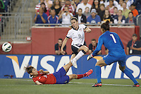USWNT midfielder Heather O'Reilly (9) centers the ball despite slide tackle by Korea Republic defender Lim Seonjoo (6). In an international friendly, the U.S. Women's National Team (USWNT) (white/blue) defeated Korea Republic (South Korea) (red/blue), 4-1, at Gillette Stadium on June 15, 2013.