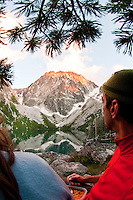 Couple eating dinner at campsite on Colchuck Lake and enjoying the last bits of alpenglow on Dragontail Peak, Alpine Lakes Wilderness, WA.