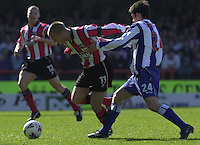 .Photo Peter Spurrier.06/04/2002.Nationwide Div 2.Brentford vs Huddersfield - Griffen Park:.Brentford's Martin Rowland on the ball, Danny Schofield trying to get on terms...