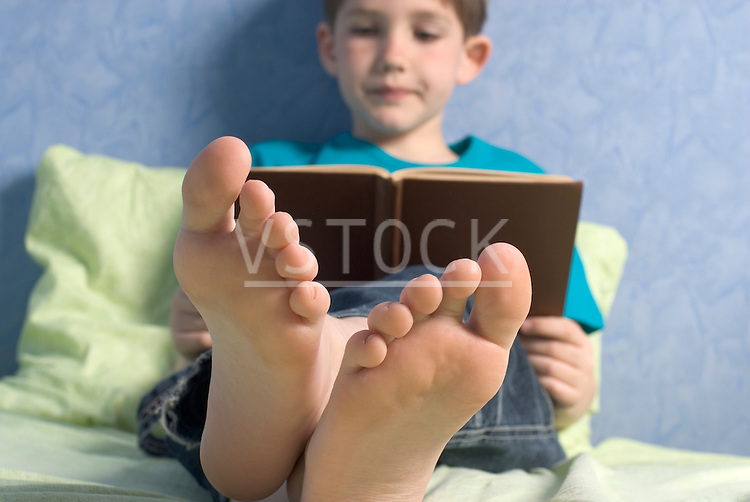 Boy (12-13) reading book on bed