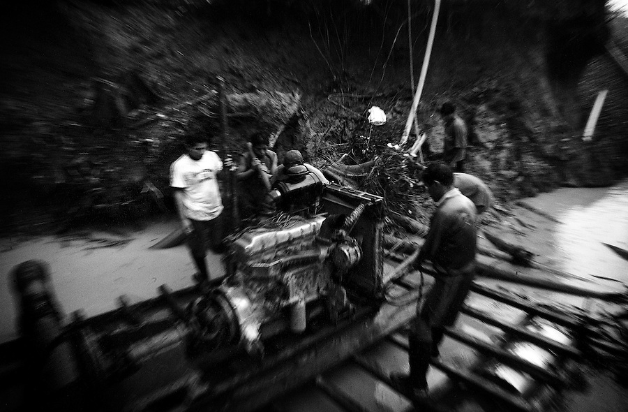 In the jungle near Laberinto Island, Peru, Feb. 8, 2007 - A group of miners pause for a moment having just transported a truck engine, re-tooled to use as a pump, onto a makeshift pontoon raft in one of the mining pits. The entire operation is very rudimentary, leaving the miners to use truck engines to pump the earth from the pit, and their own ingenuity and physical strength to make due for the rest. The miners of this crew work in 24-hour shifts, one day on and one day off, earning on average 1 1/2 to 2 grams of gold per day, or about $30 to 45 dollars. .