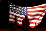 Two boys are silhouetted against a huge American Flag as they sit on the interstate parapet during Williamsport, PA's annual Fourth of July celebration.