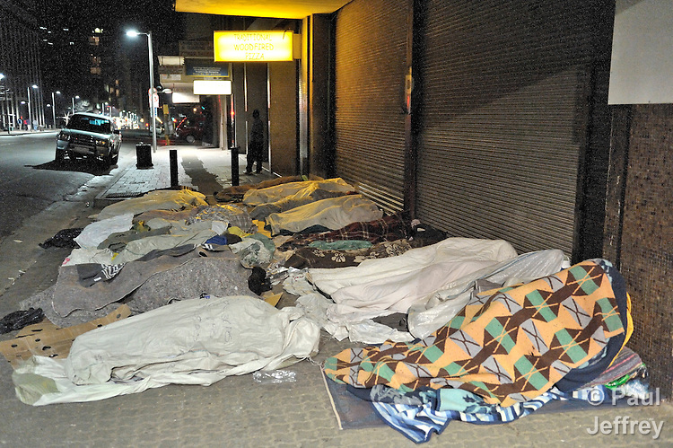 Refugees from Zimbabwe and other African countries sleeping on the streets around the Central Methodist Church in Johannesburg, South Africa. The church is home to more than 3,000 refugees suffering from economic desperation and sporadic xenophobic attacks. Since all cannot fit into the church at night, the overflow spreads out on neighboring sidewalks.