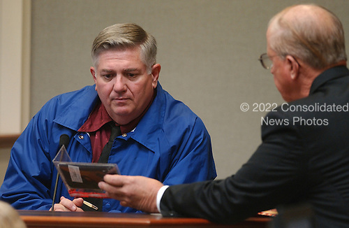 Prince William County (Virginia) prosecutor Paul Ebert, right, shows James Ballenger, widower of Hong Im Ballenger, a planner during his testimony at the trial of Sniper suspect John Allen Muhammad, at the Virginia Beach Circuit Court  in Virginia Beach, Virginia on October 24, 2003. <br /> Credit: Davis Turner - Pool via CNP