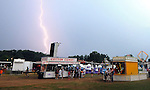People huddle nears some booth overhangs as a fast moving but strong electrical stormed passed through the area, Friday evening during second night of Suffield Fire Department Annual Carnival on Mountain Rd (Jim Michaud/Journal Inquirer)