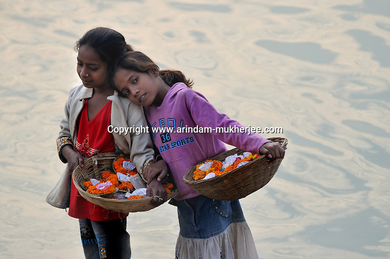Young Indian flower seller. They will sell the flowers to the pilgrims and ultimately these flowers will be thrown in the river ganges. Varanasi, Uttar Pradesh, India.