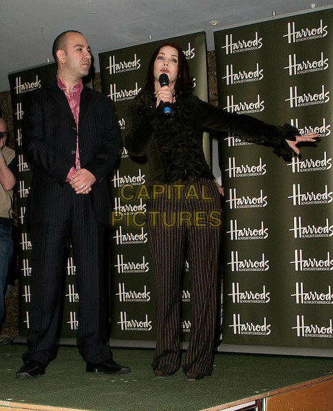 BRUNO SCHIAVI & PRISCILLA PRESLEY.Press launch & photocall, Bed Linen department (2nd floor), Harrods, London, UK..April 5th, 2006.Ref: AH.full length brown ruffles black suit pinstripe trousers microphone.www.capitalpictures.com.sales@capitalpictures.com.© Capital Pictures.