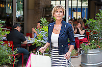 Female shopper walking past a sidewalk cafe restaurant at an Austin outdoor shopping mall