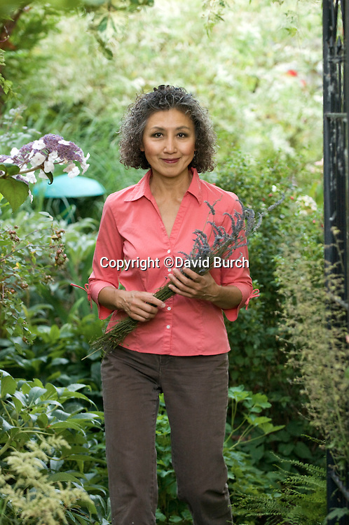 Asian woman in her garden holding lavandar, smiling