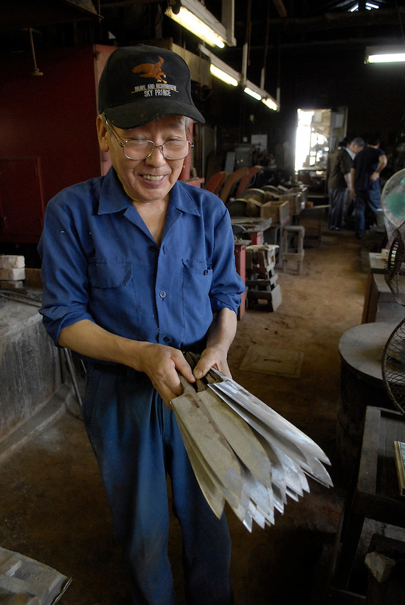 A worker at the  Takahashi knife workshop hold unfinished cooking knives.The company makes cooking knives for the shop in Tsukiji fish market..