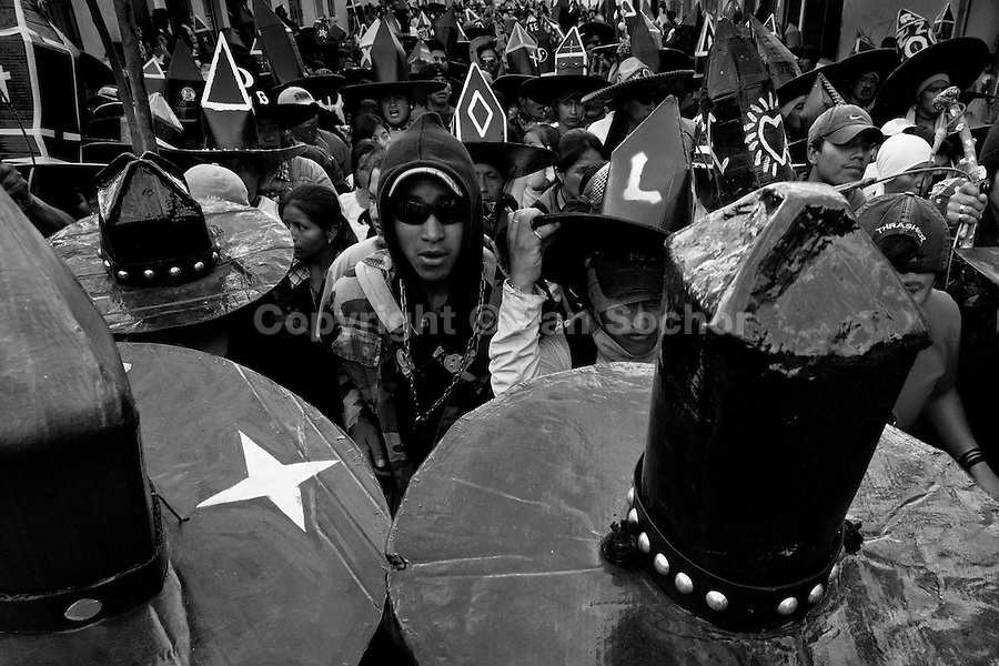 Indians, wearing black cardboard hats, dance during the Inti Raymi (San Juan) festivities in Cotacachi, Ecuador, 29 June 2010. 'La toma de la Plaza' (Taking of the square) is an ancient ritual kept by Andean indigenous communities. From the early morning of the feast day, various groups of San Juan dancers from remote mountain villages dance in a slow trot towards the main square of Cotacachi. Reaching the plaza, Indians start to dance around. They pound in synchronized dance rhythm, shout loudly, whistle and wave whips, showing the strength and aggression. Dancers from either the upper communities (El Topo) or the lower communities (La Calera), joined in respective coalitions, seek to conquer and dominate the square and do not let their rivals enter. If not moderated by the police in time, the high tension between groups always ends up in violent clashes.