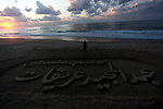 """Palestinian artist, Ibrahim Hamad paints on the sand sculpture reads in Arabic """"Abdel Majeed Orikat, at the beach of Gaza city on December 7, 2019. Photo by Mahmoud Ajjour"""