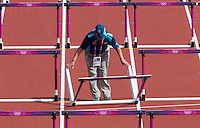 03 AUG 2012 - LONDON, GBR - Technical Official Jan Lishman repositions a hurdle between 100m hurdles heats during the women's heptathlon at the London 2012 Olympic Games athletics in the Olympic Stadium in the Olympic Park in Stratford, London, Great Britain (PHOTO (C) 2012 NIGEL FARROW)