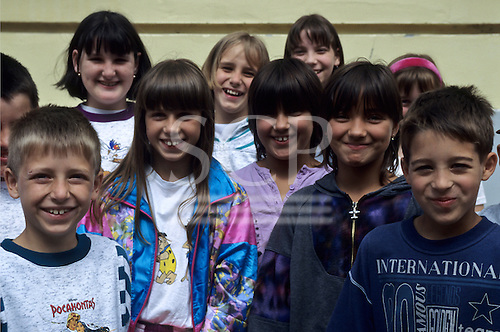 "Hungary. Group of smiling schoolchildren, one with an ""international"" sweatshirt."