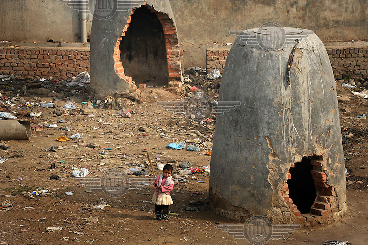 A small child wanders past turrets in a slum in the area of Nizamuddin East.