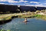 Woman soaking in Trego hot ditch
