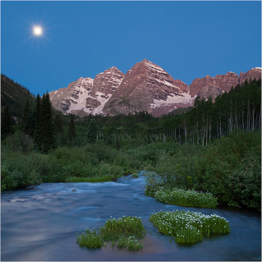 Well before sunrise, the full moon was setting over the iconic Maroon Bells. This image of the landscape taken in from the creek that flows from Crater Lake to Maroon Lake on an early summer morning. It was one of the rare times you can enjoy the Maroon Bells wilderness area nearly all to yourself!