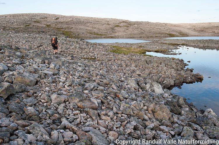 Dame går til fots i goldt fjellterreng på Nordkynn. ---- Woman hiking in rocky terrain.
