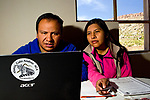 Andean Mountain Cat (Leopardus jacobita) biologists, Juan Carlos Huaranca Ariste and Alejandra Rocio Torrez Tarqui, looking at camera trap images on computer, Ciudad de Piedra, Andes, western Bolivia
