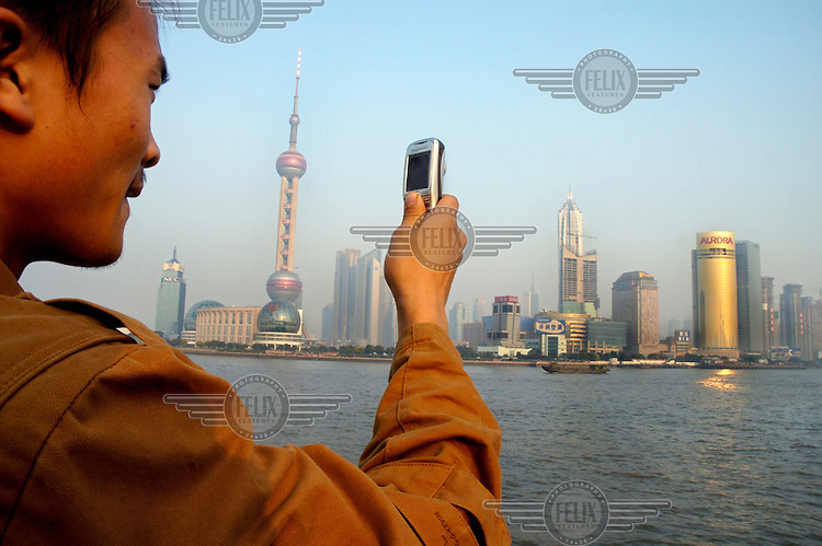Young man on the Bund taking a photograph with his Sony Ericsson mobile telephone of Pudong Financial District on the far side of the Huangpu River, with the Oriental Pearl TV Tower at left and the 88 floor Jin Mao Tower, the tallest building in China, at right.