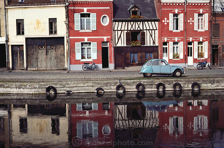 Old houses, two mobilettes, and a Deux Chevaux car alongside a canal in Amiens, France.