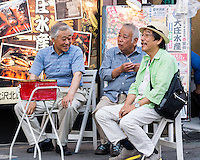 "Three oyaji are talking in a smoking area. Oyaji means ""old man"" in Japanese. These men are most likely retired. They are enjoying a warm summer evening with some talk and cigarettes."