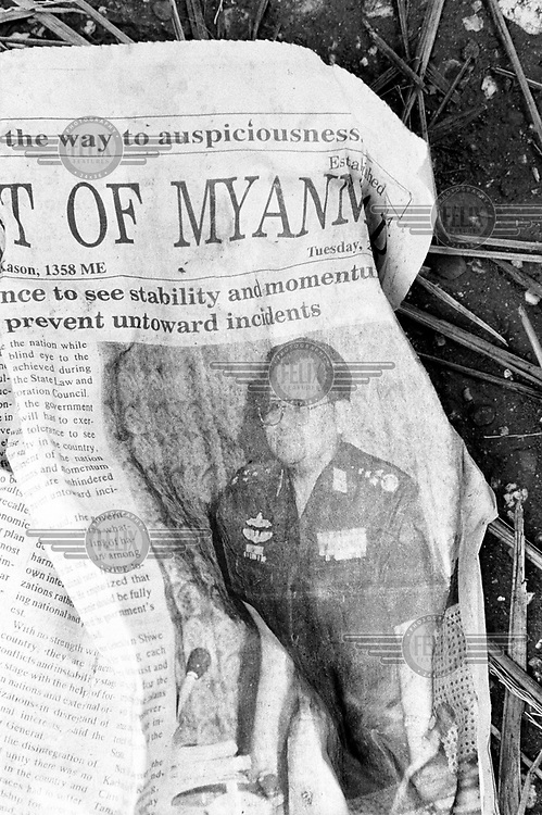 A cover of the junta's English language newspaper, 'The New Light of Myanmar', is discarded as litter on a Rangoon street. The paper is reporting on the activities of Senior General Than Shwe.