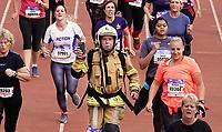 Nederland - Amsterdam - 2019 . De Marathon van Amsterdam. De finish in het Olympisch Stadion. Brandweerman van Apollo Vredestein rent de wedstrijd in uniform inclusief helm.   Foto Berlinda van Dam / Hollandse Hoogte