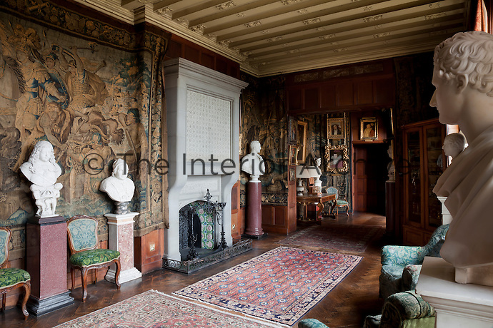 A panelled hallway lined with tapestries and marble busts