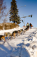 Linwood Fiedler  and team run past spectators and down the Cordova Street hill with an Iditarider in the<br /> basket and a handler during the Anchorage, Alaska ceremonial start on Saturday March 4th<br /> during the 2017 Iditarod race. Photo  @2017 by Kristie Lent/ SchultzPhoto.com