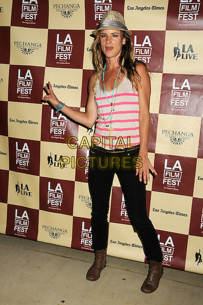 "Juliette Lewis.2011 Los Angeles Film Festival Screening of ""Beats, Rhymes & Life: The Travels Of A Tribe Called Quest"" held at the John Anson Ford Amphitheatre, Los Angeles, California, USA, .24th June 2011..full length striped black jeans  brown ankle boots hand  v gesture peace sign necklace hat  turquoise beads pink grey gray vest .CAP/ADM/BP.©Byron Purvis/AdMedia/Capital Pictures."