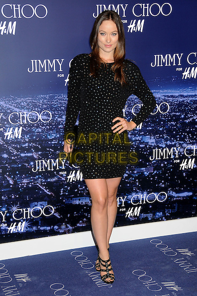 OLIVIA WILDE.Jimmy Choo for H&M Launch Party held at a Private Residence, West Hollywood, California, USA..November 2nd, 2009.full length dress long sleeve sleeved black beaded beads sparkly clutch bag gladiator studded studs sandals hand on hip .CAP/ADM/BP.©Byron Purvis/AdMedia/Capital Pictures.