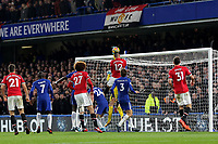 Chris Smalling of Manchester United leaps into the air to challenge Chelsea goalkeeper, Thibaut Courtois during Chelsea vs Manchester United, Premier League Football at Stamford Bridge on 5th November 2017