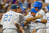 UCLA Bruin pinch runner Christoph Bono (3) is greeted by his teammates after he scored the winning run in the eighth inning of Game 4 of the 2013 Men's College World Series against the LSU Tigers on June 16, 2013 at TD Ameritrade Park in Omaha, Nebraska. UCLA defeated LSU 2-1. (Andrew Woolley/Four Seam Images)