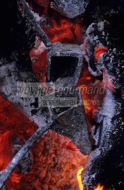 """Europe/France/Midi-Pyrénées/12/Aveyron/La Cresse : Ferme auberge """"La Tindelle"""" de Loïc et René Almeras -  Cuisson d'une poularde au capucin (ustensile de cuisine que l'on fait chauffer dans un foyer et que l'on rempli de graisse que l'on enflamme pour cuire """"à la graisse coulée"""" les gibiers et volaille)"""