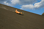 Backpacker boarding down the active Volcano Cerro Negro, Nicaragua
