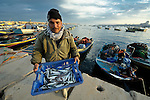 A fisher unloads his catch after a night of fishing off Gaza's coastline. Under the 1993 Oslo Peace Accords, the people of Gaza were allowed to fish out to 20 nautical miles from their coastline, yet since the Israeli military imposed a naval blockade in 2007 they have been limited to just three nautical miles. In practice, fishers who venture beyond two nautical miles are shot at by Israeli gunboats; several have been injured and some killed. Despite having 40 kilometers of coastline and a long tradition as fishers, many fishers are unemployed and the people of Gaza are forced to import fish from Israel. And what fishing they can do close to shore mostly involves the harvest of immature fish, which biologists warn has a negative impact on fish stocks in the region....