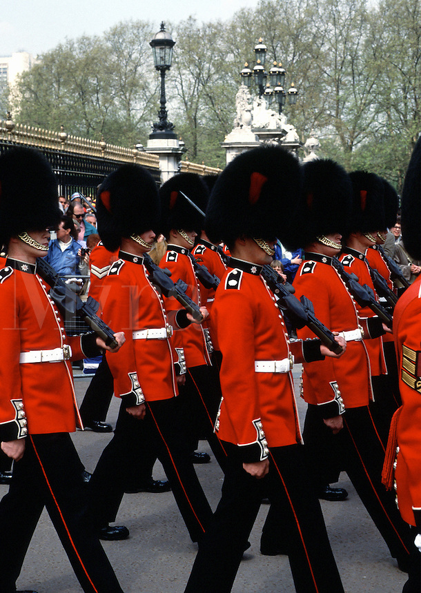 The traditional Changing of the Guards at Buckingham Palace as tourists look on. London, England.
