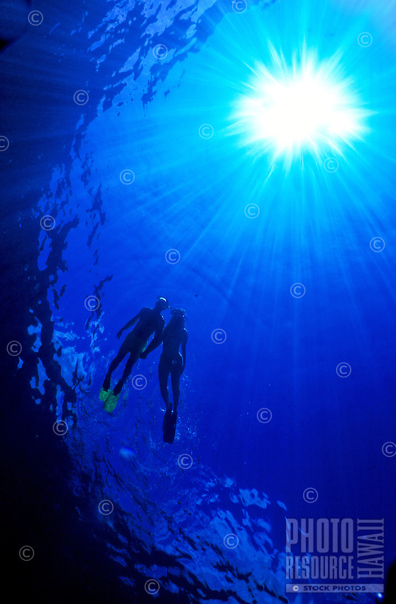 A couple snorkels in the inviting waters of Hanauma Bay, Oahu.  A sunburst outlines their silhouette.