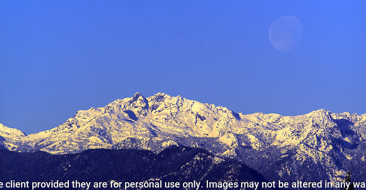 A full moon sets over the Olympic mountains area in Washington's Olympic National Park. The Olympic Mountains is a year-round destination. In summer, visitors come for views of the Olympic Mountains, as well as for superb hiking. During the winter months the small, family oriented Hurricane Ridge Ski and Snowboard Area offers lift-serviced downhill skiing and snowboarding. Hurricane Ridge is named for its intense gales and winds. The weather in the Olympic Mountains is unpredictable, and visitors should be prepared for snow at any time of year. Jim Bryant Photo. ©2017. All Rights Reserved.