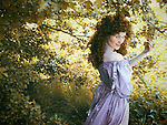 A woman in a period gown,long dark curly hair and a  flirty facial expression, standing under a tree and touching one of the branches.
