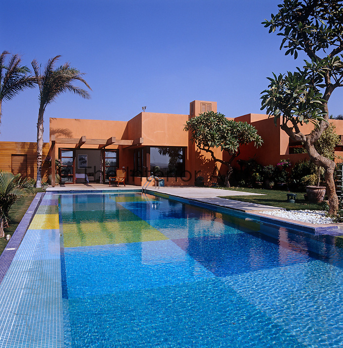 The bright blue mosaic tiling of the large outdoor swimming pool shimmers in the Egyptian sun in vivid contrast to the brick-red plaster walls of the house